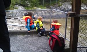 3 barn i ivrig samtale, kledt i flytevester, ved brygga på Solvik