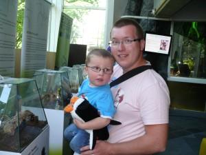 Far med liten gutt på armen ved edderkopp-terariumene.