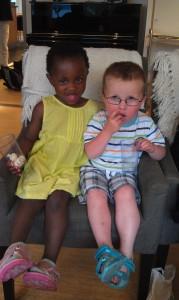 To barn sitter sammen i en lenestol og deler chips.