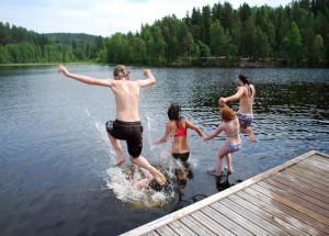 Badende barn hopper fra bryggekanten