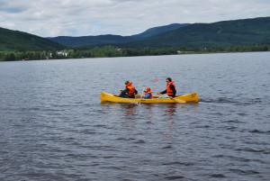 To voksne og et barn padler kano på stille vann