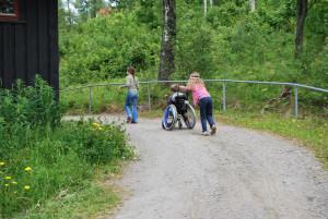 To jenter trille en gutt i rullestol opp en bakke