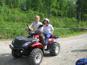 Eldre dame sitter på med ung mann på en ATV (firhjuling)