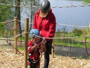 Barn i klatreutstyr, med voksen
