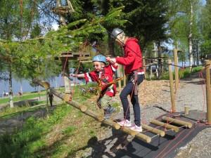 Barn i klatreutstyr på vei opp taustige, med hjelp av voksen