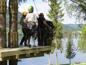 Tre voksne venter på tur over hengebro, på platform høyt over bakken