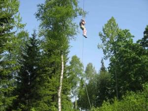 Person i full fart i zipline, høyt over bakken
