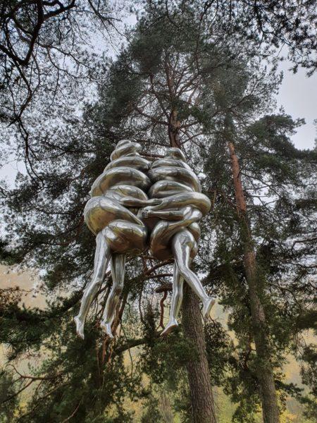 Ekeberg skulpturpark: Hengende skulptur; To softismennesker som henger sammen med beina stikkende ut nede.