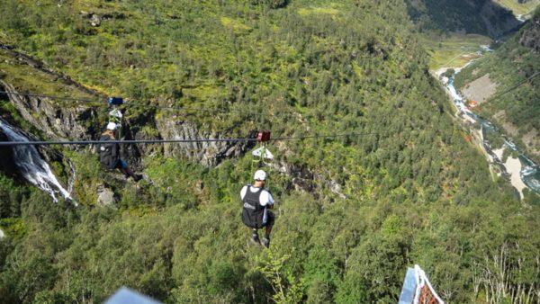 To personer i fart på vei ned zipline høyt over bakken.