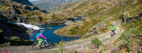 Syklister på Rallarvegen med majestetisk fjell-landskap i bakgrunnen.